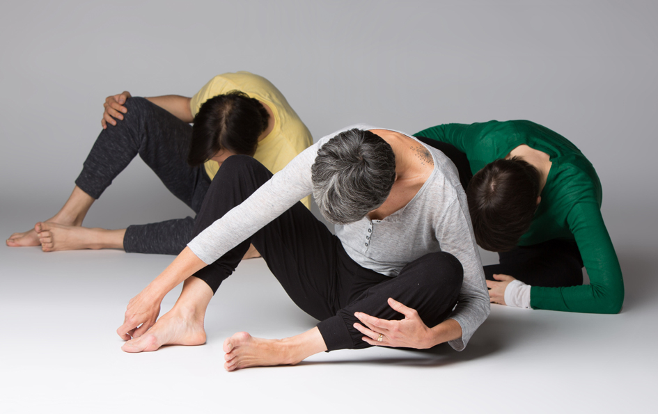 Trois élèves assis au sol, jambes à moitié repliées penchent la tête vers le sol en étirant leur colonne vertébrale.