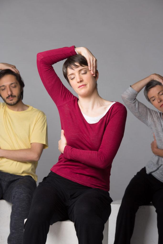 Trois élèves assis, la main gauche sur le flanc droit, le bras droit levé, poignet au-dessus de la tête et main sur la tempe gauche.